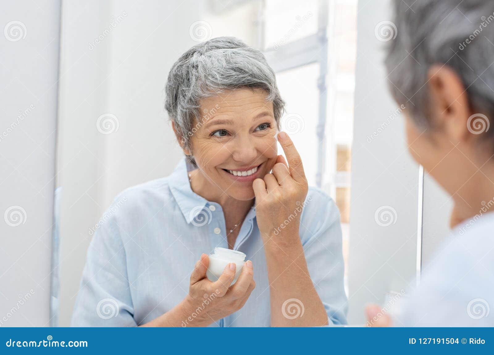Mujer mayor que aplica la crema antienvejecedora