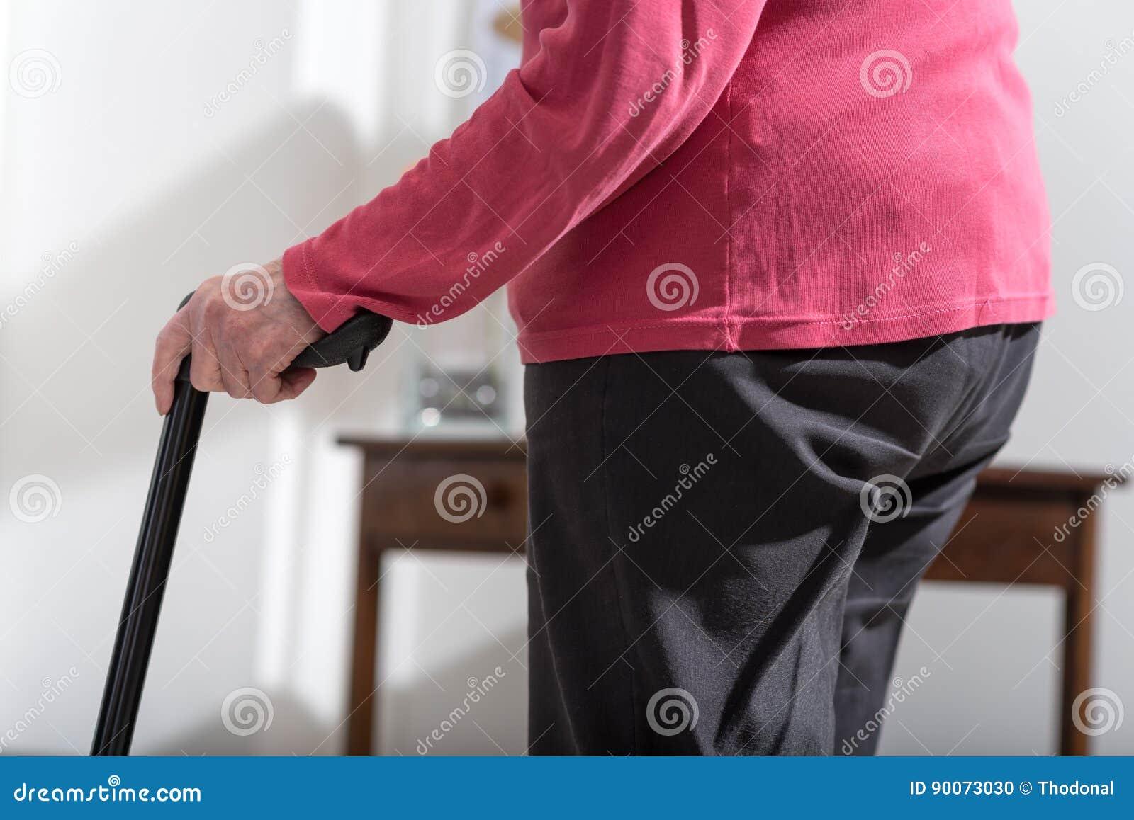 Mujer mayor que camina con un bastón