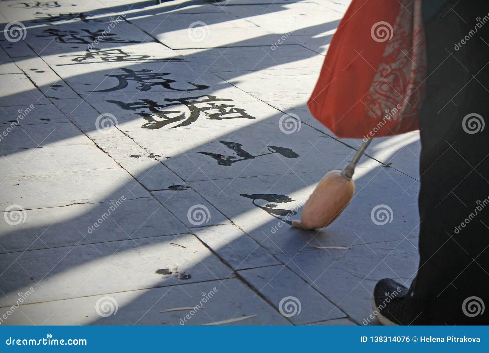 Mujer mayor que escribe la caligrafía china
