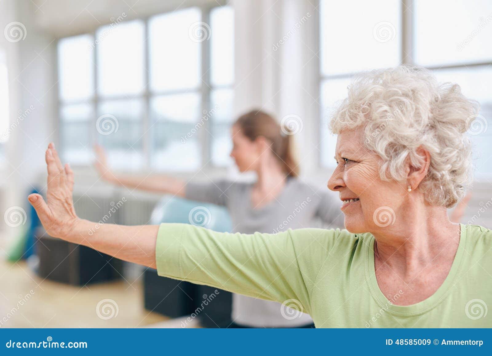 Mujer mayor que hace estirando ejercicio en la clase de la yoga