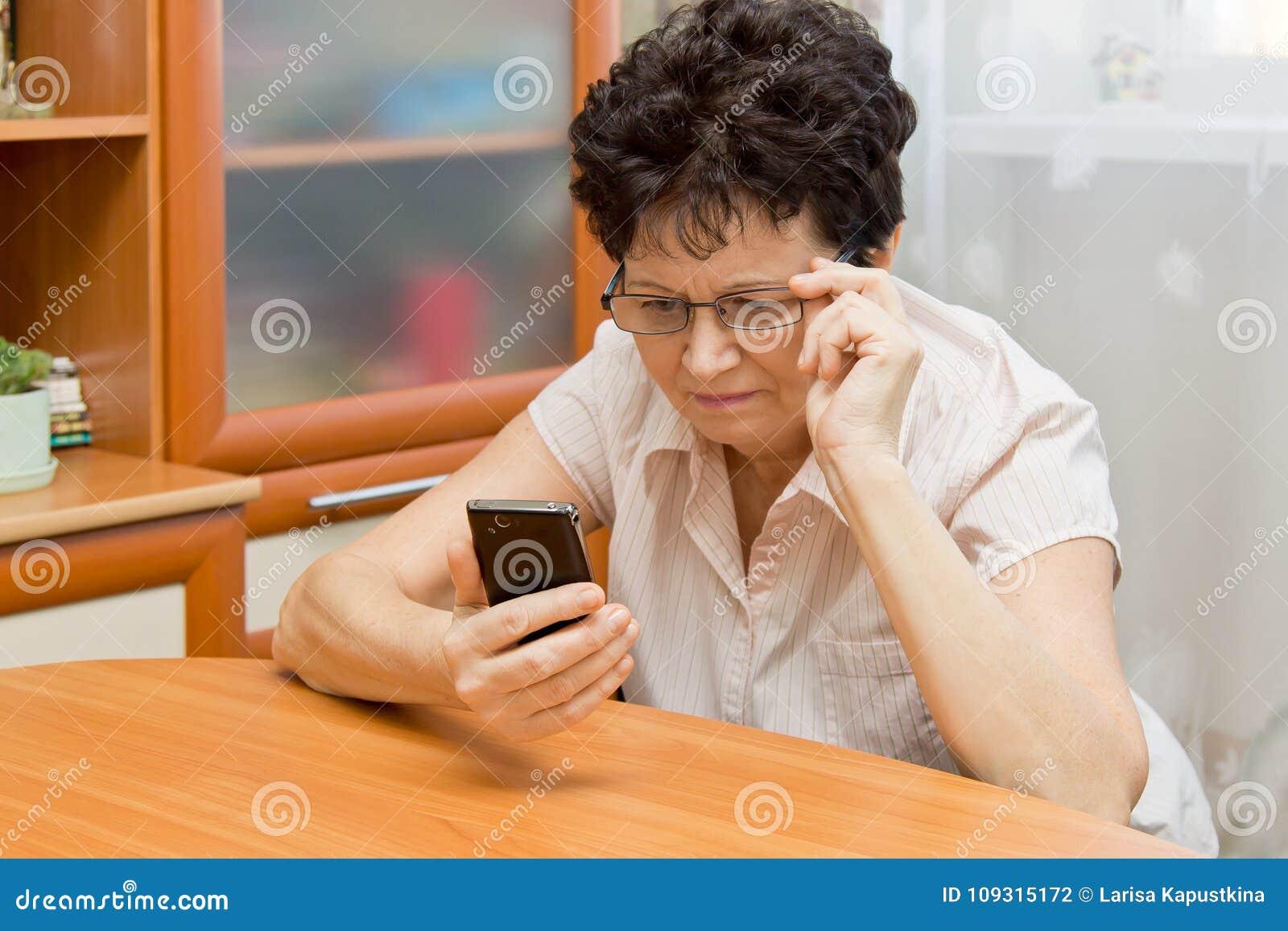 Mujer mayor que mira de cerca la pantalla del teléfono, intentando ver qué se escribe allí
