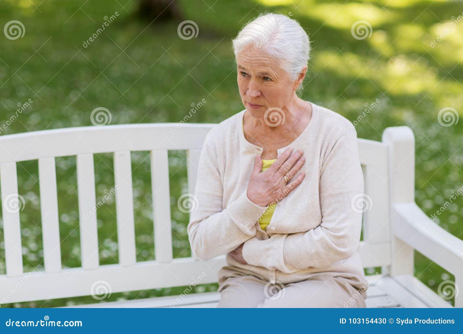 Mujer mayor que siente enferma en el parque del verano