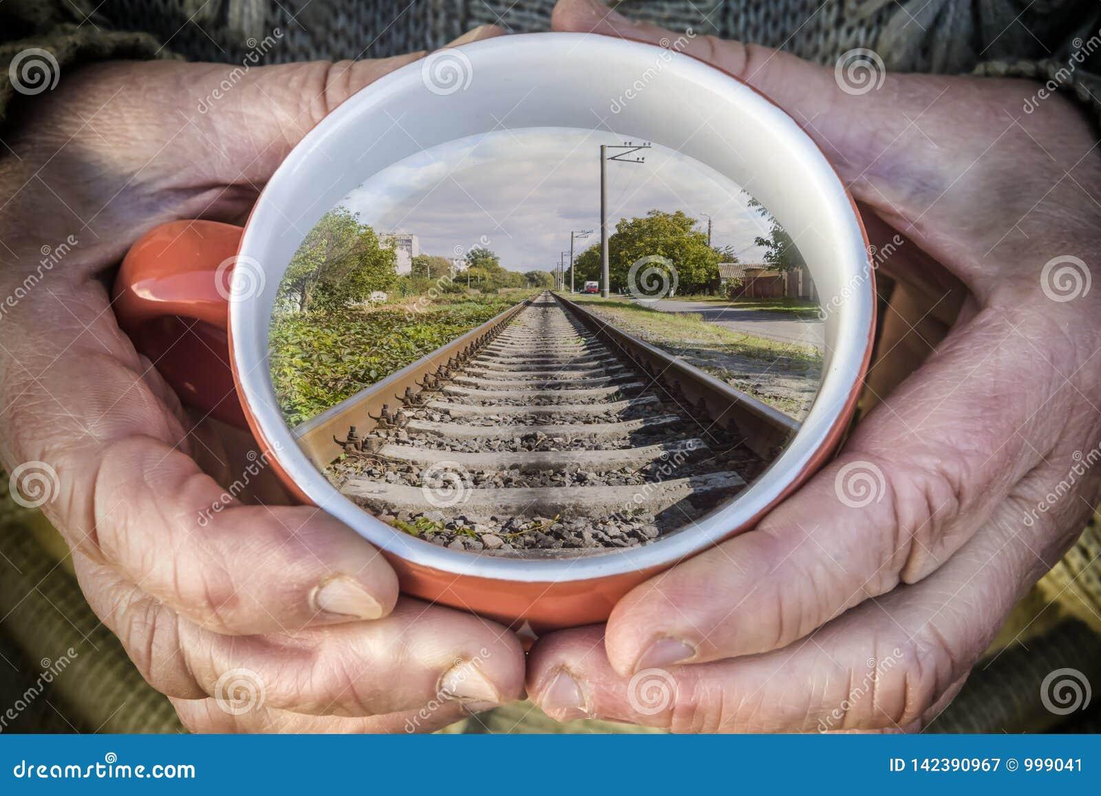 Mujer mayor que sostiene una taza de té El círculo refleja los carriles del tren
