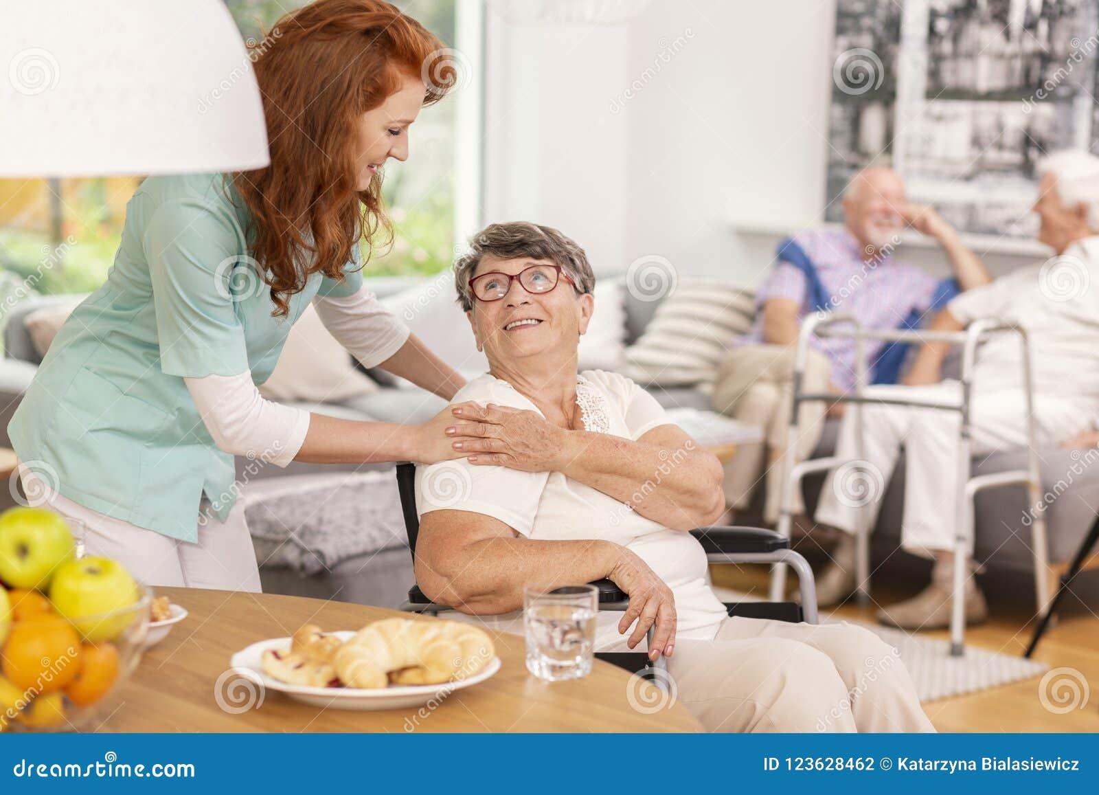 Mujer mayor sonriente favorable de la enfermera amistosa en casa del oficio de enfermera