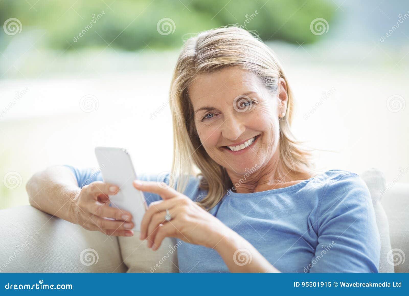 Mujer mayor sonriente que usa el teléfono móvil en sala de estar