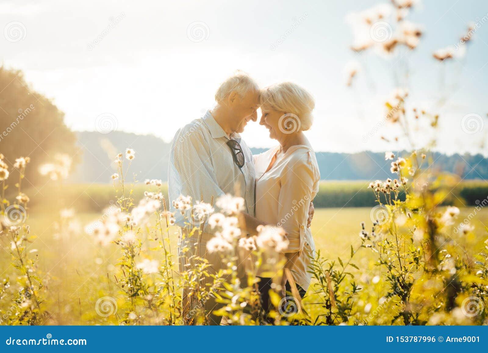 Mujer mayor y hombre que abrazan todavía estar en amor