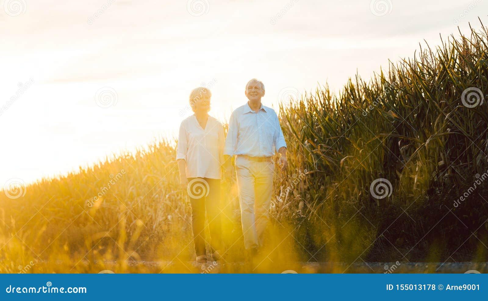 Mujer mayor y hombre que tienen un paseo a lo largo de un campo
