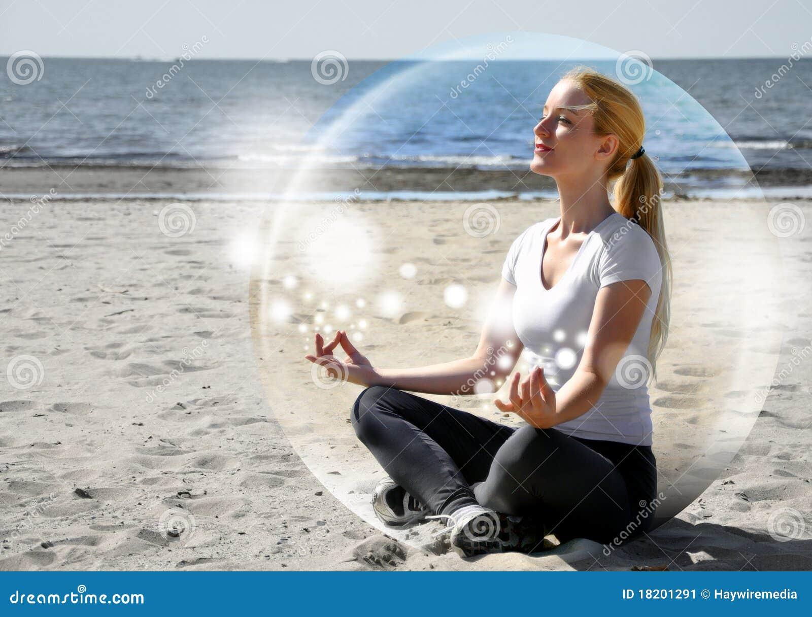 Mujer Meditating en la playa en paz