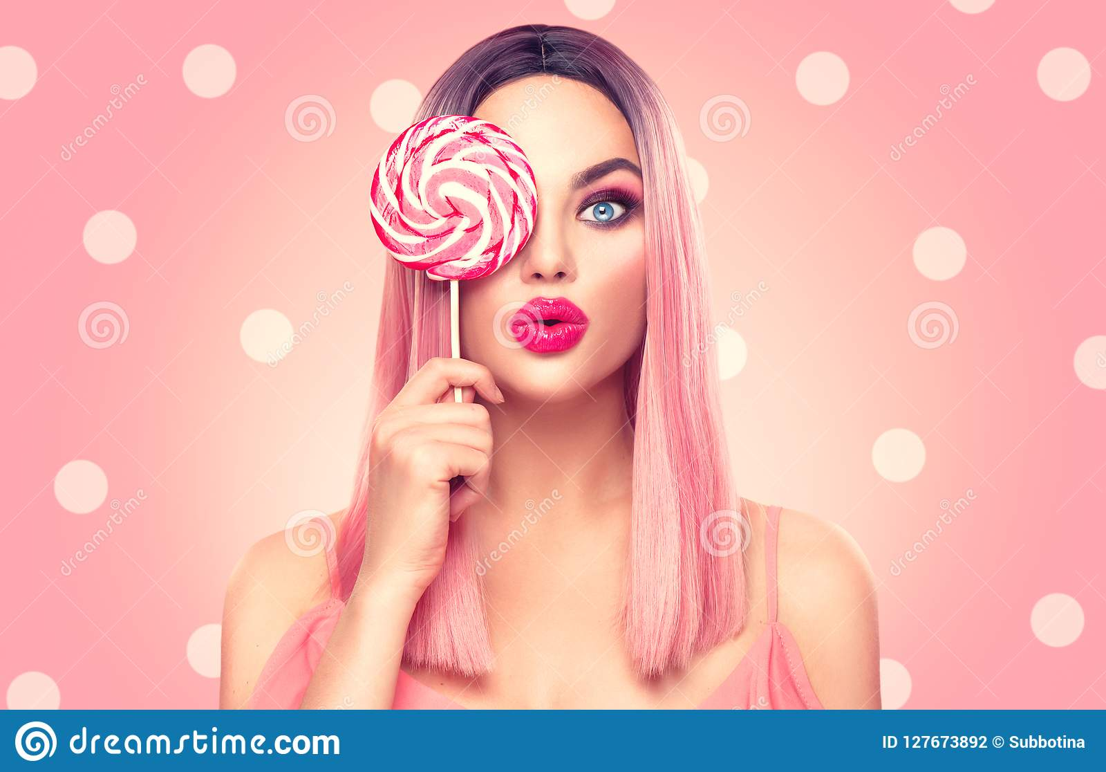 Mujer modelo atractiva de la belleza con el peinado rosado de moda y el maquillaje hermoso que sostienen el caramelo de la pirule