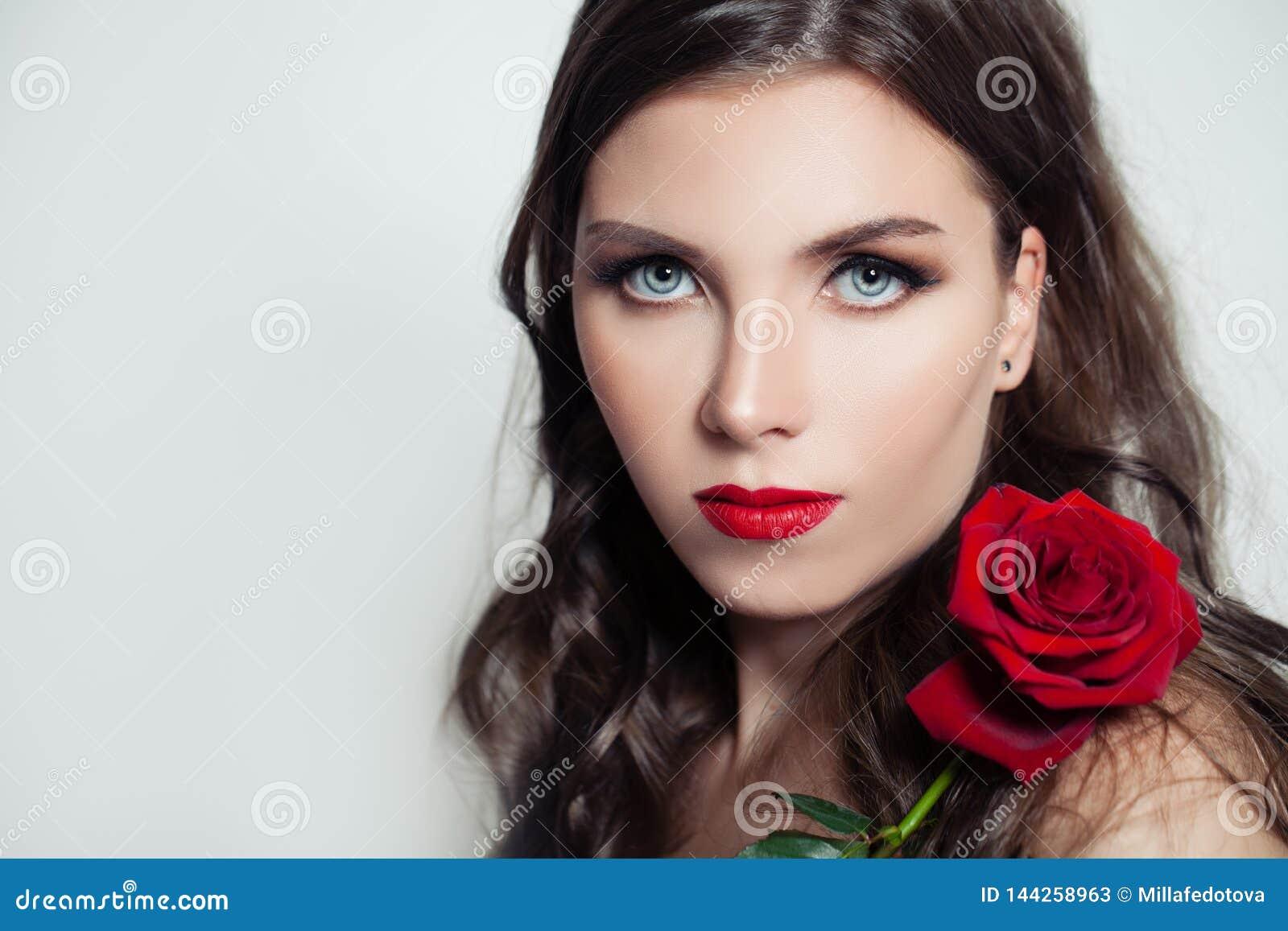 Mujer modelo linda con el maquillaje rojo de los labios que sostiene la flor color de rosa roja