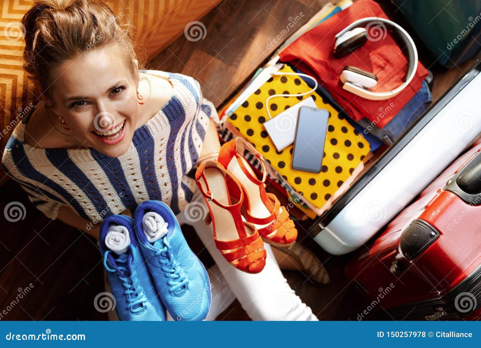 Mujer moderna sonriente que embala los zapatos atractivos y cómodos