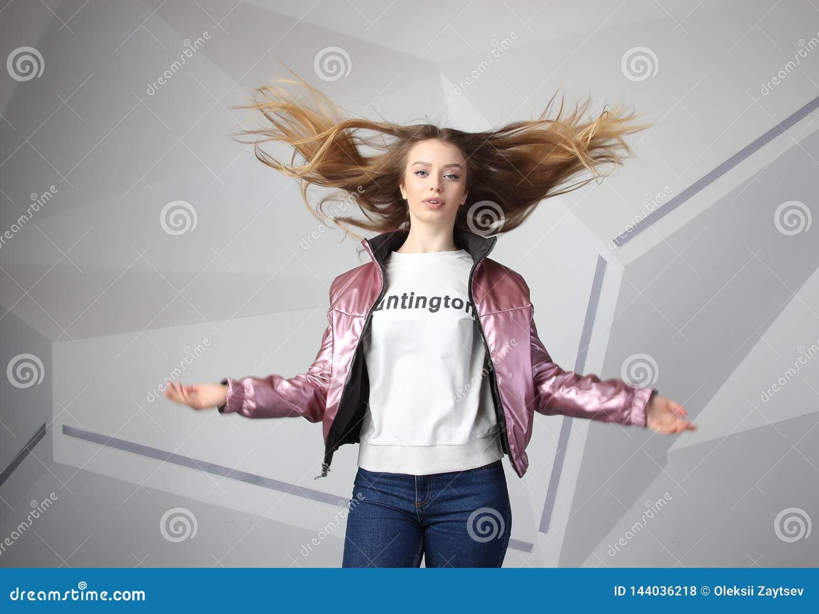 Mujer morena agresiva furiosa de griterío con volar los pelos largos, retrato de destello del estudio en la pared moderna