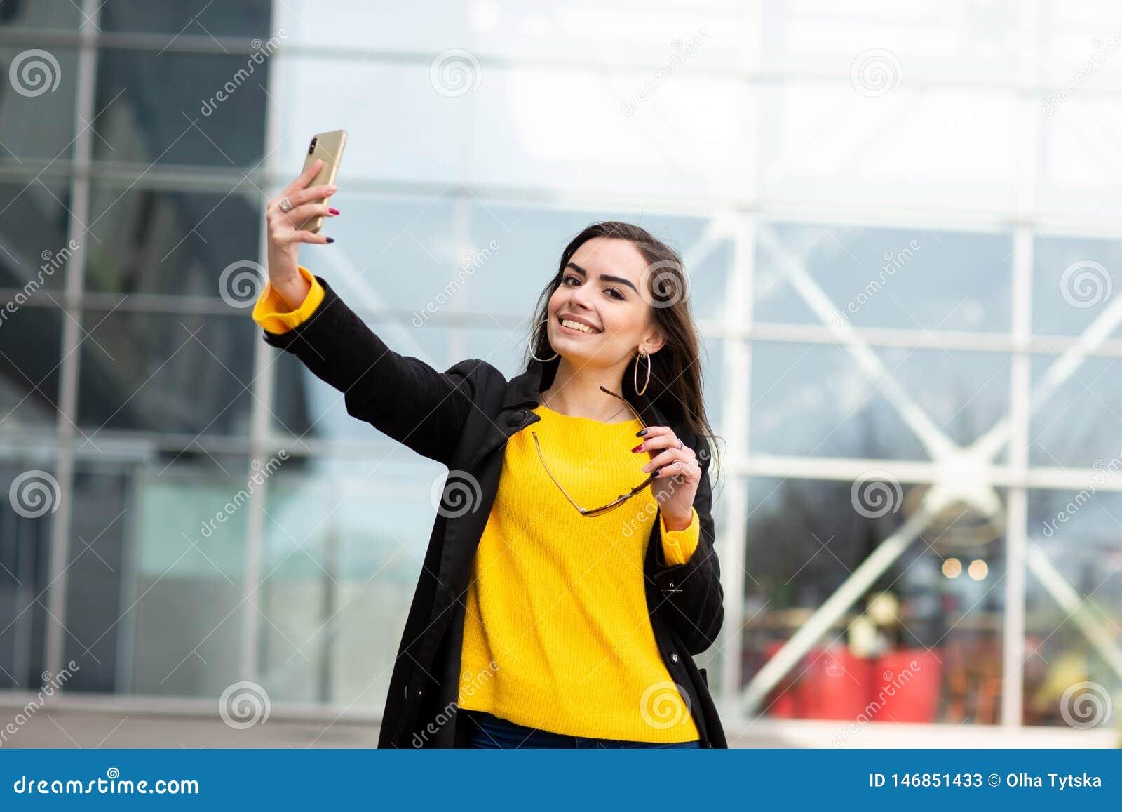Mujer morena alegre en el su?ter amarillo que hace el sefie contra fondo del aeropuerto Tecnolog?a moderna