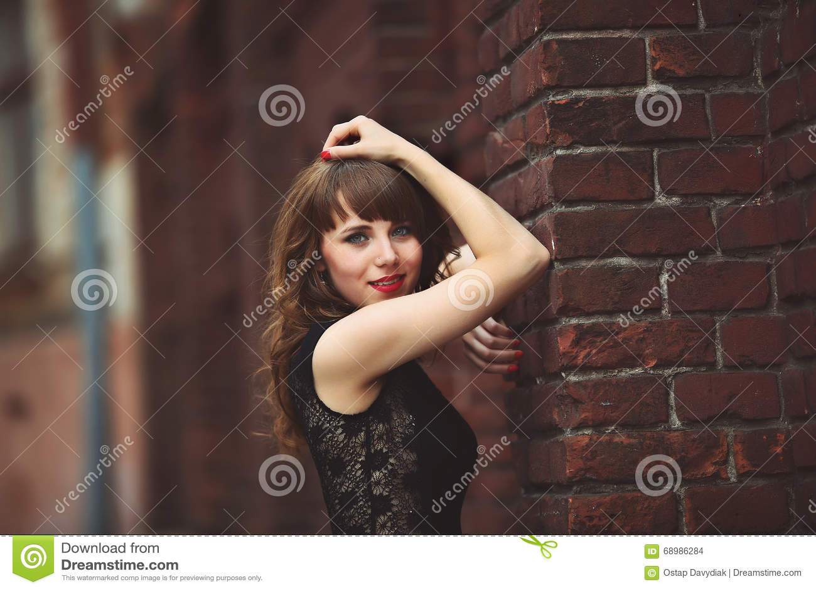 Mujer morena atractiva hermosa que se coloca cerca de una pared de ladrillo en dres