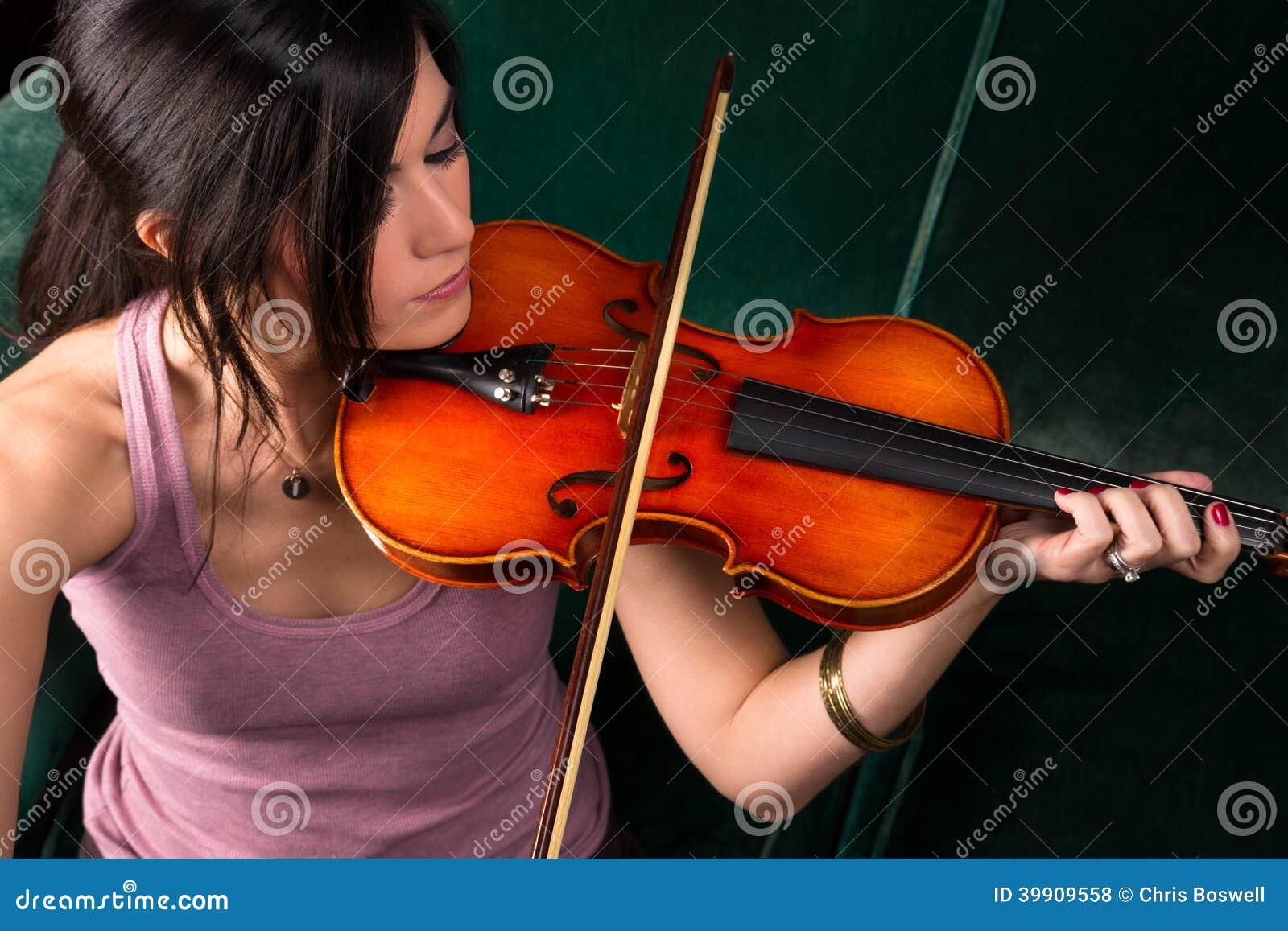 Mujer morena atractiva sensual que toca el instrumento atado acústico del concierto