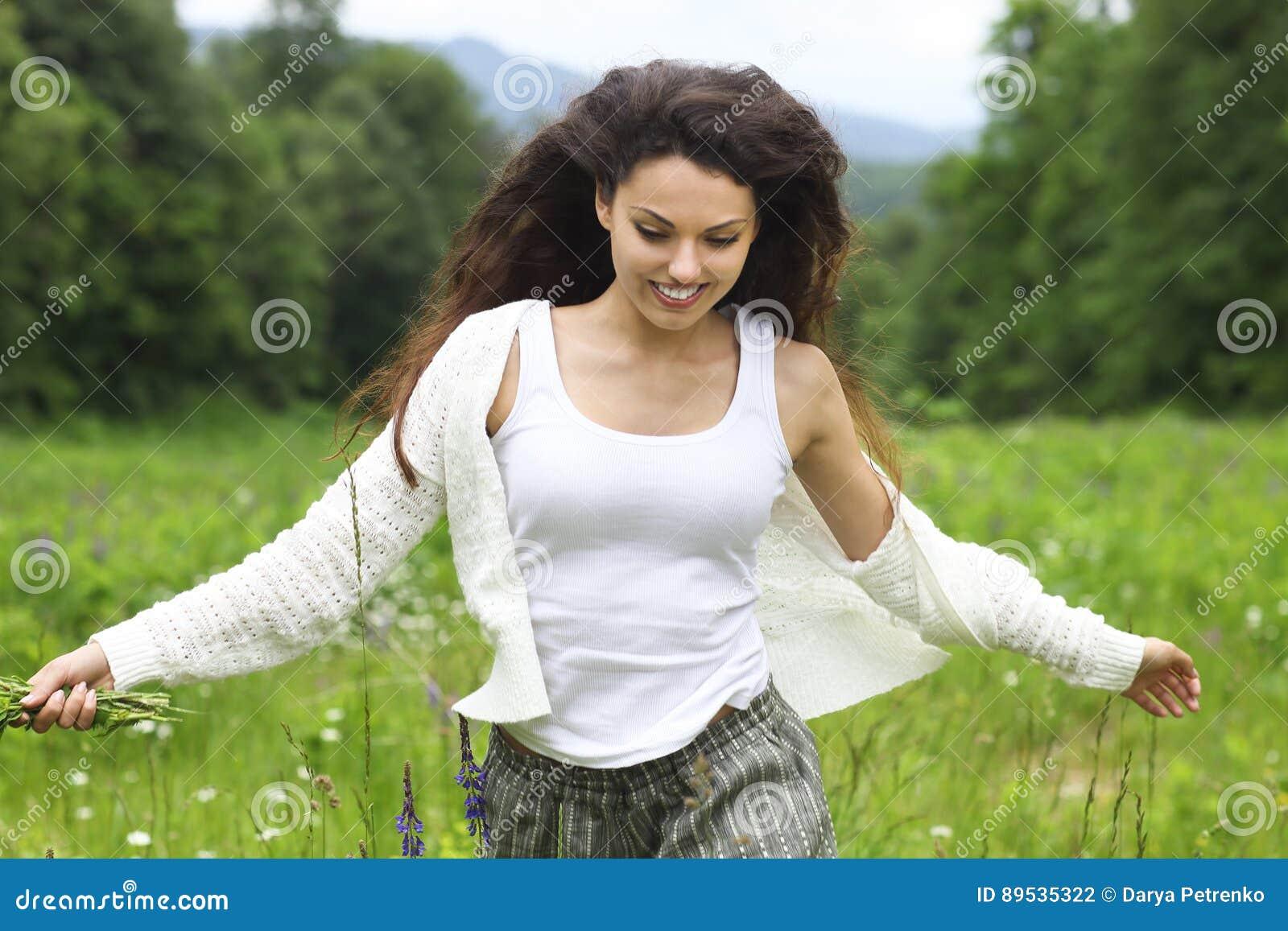 Mujer morena bonita feliz en el campo de la manzanilla, real femenino lindo