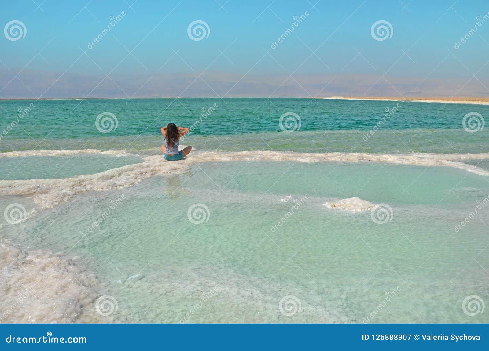 Mujer morena de pelo largo que se sienta en la sal riegue la superficie del mar muerto en Israel con la vista de la montaña Jorda