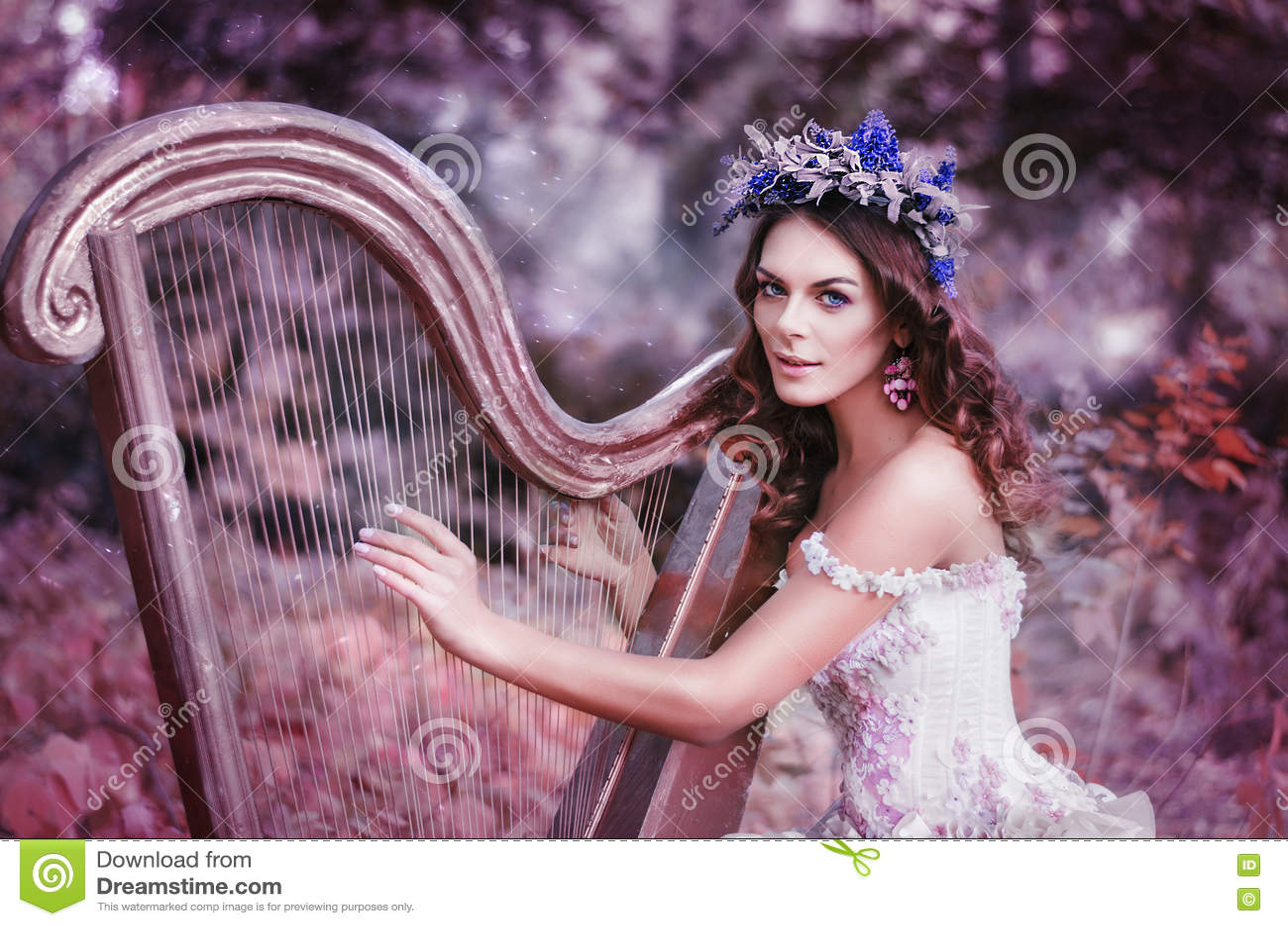 Mujer morena hermosa con una guirnalda de la flor en su cabeza, llevando un vestido blanco que toca la arpa en el bosque