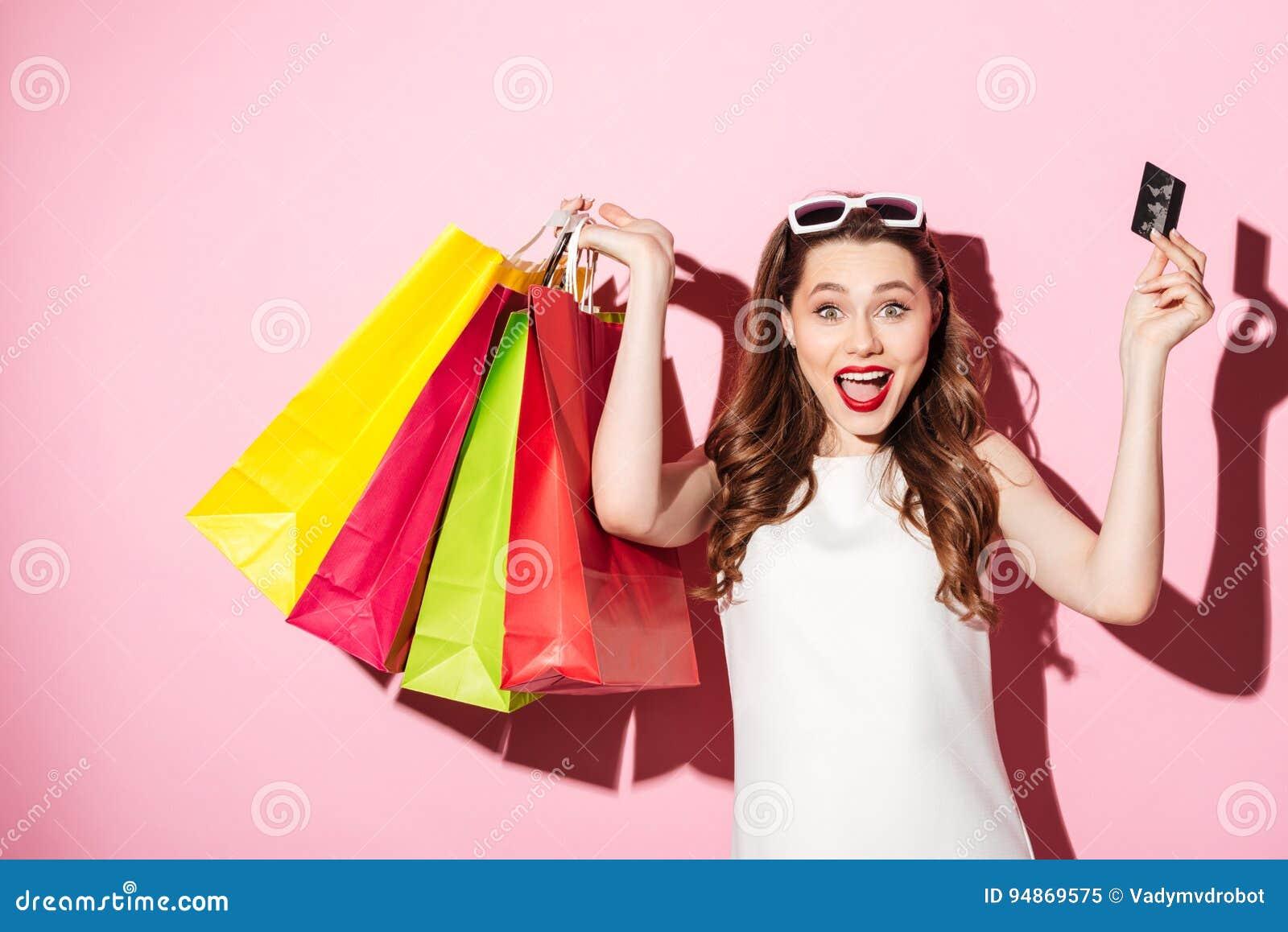 Mujer morena joven feliz que sostiene la tarjeta y los panieres de crédito