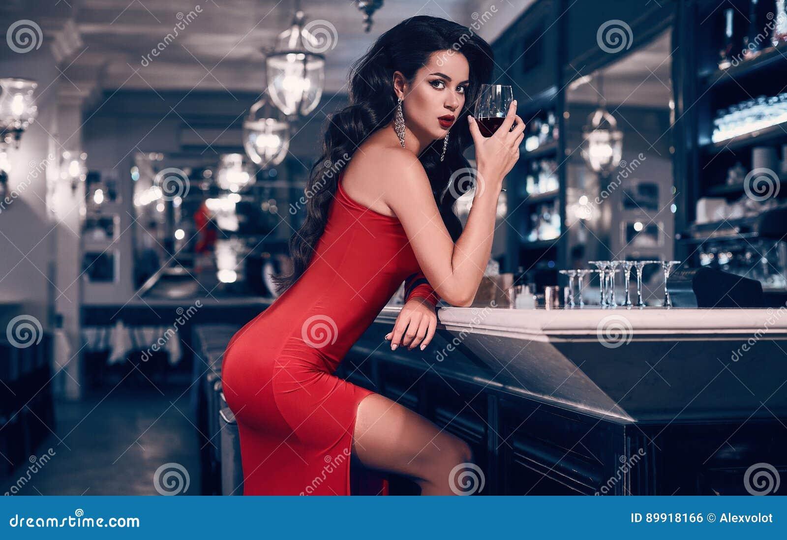 Mujer morena joven magnífica en vestido rojo con el vino