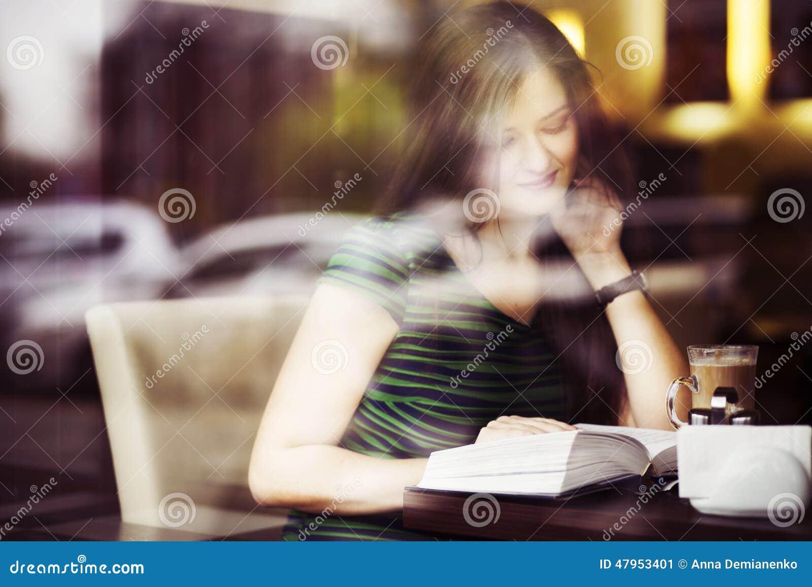 Mujer morena que se sienta en el café del libro de lectura del café, el studing y de la consumición