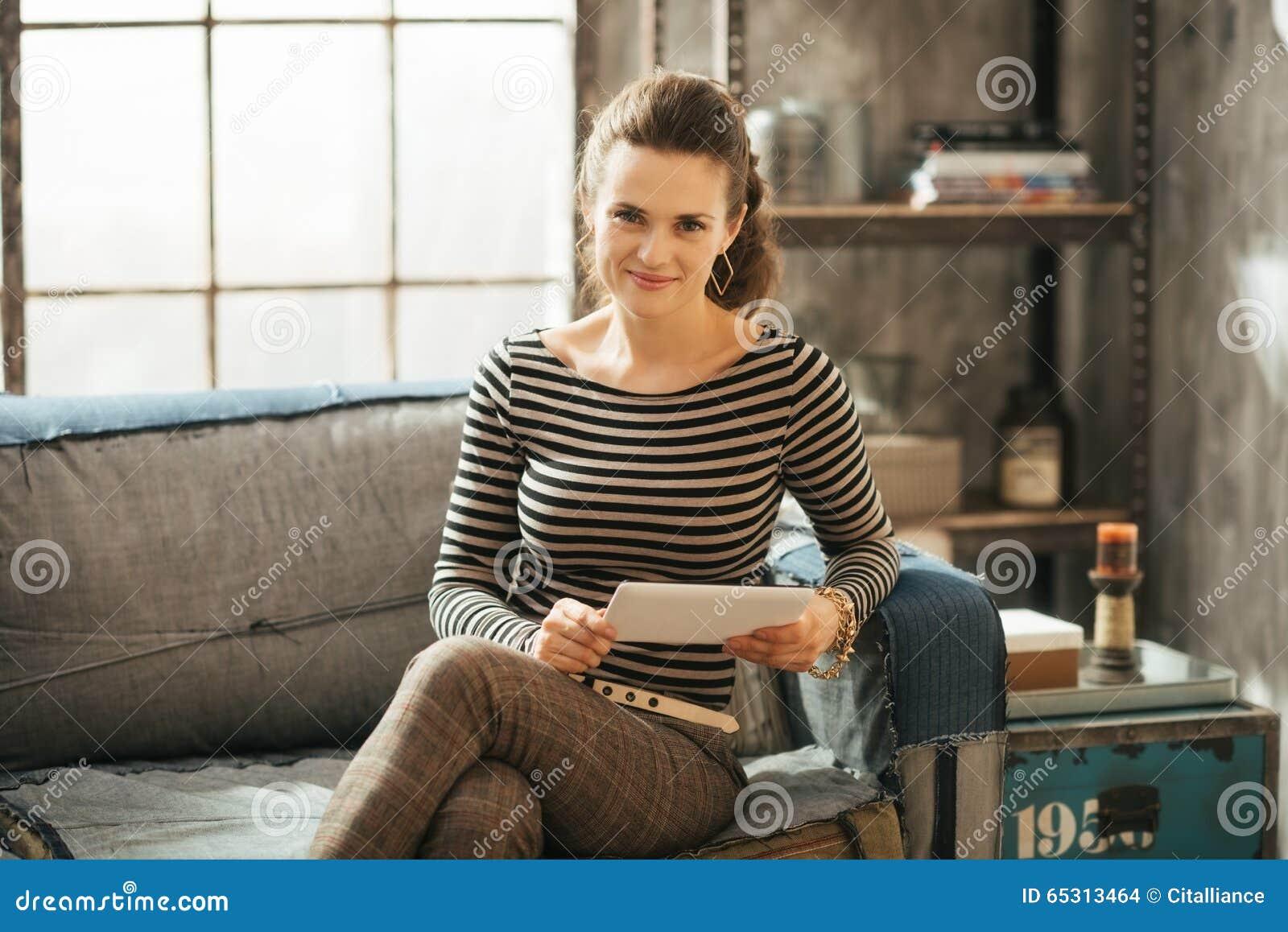 Mujer morena rica joven que se sienta en el sofá y que sostiene la tableta
