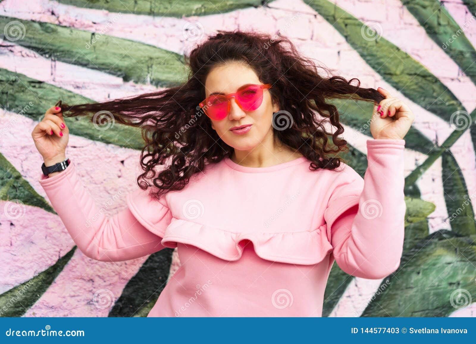 Mujer morena rizada de pelo largo en vestido rosado y vidrios rosados