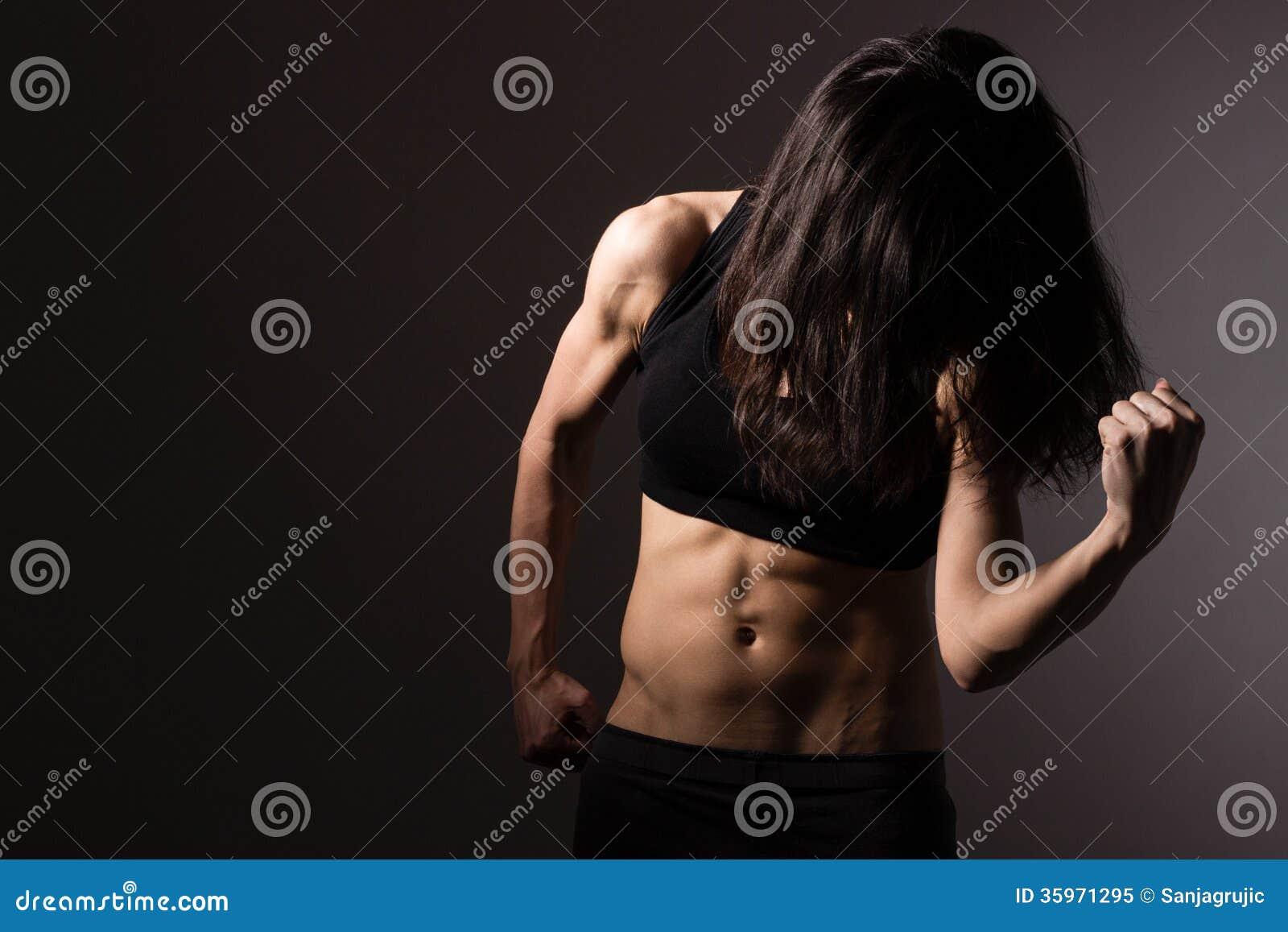 Mujer muscular del ajuste que muestra el bíceps