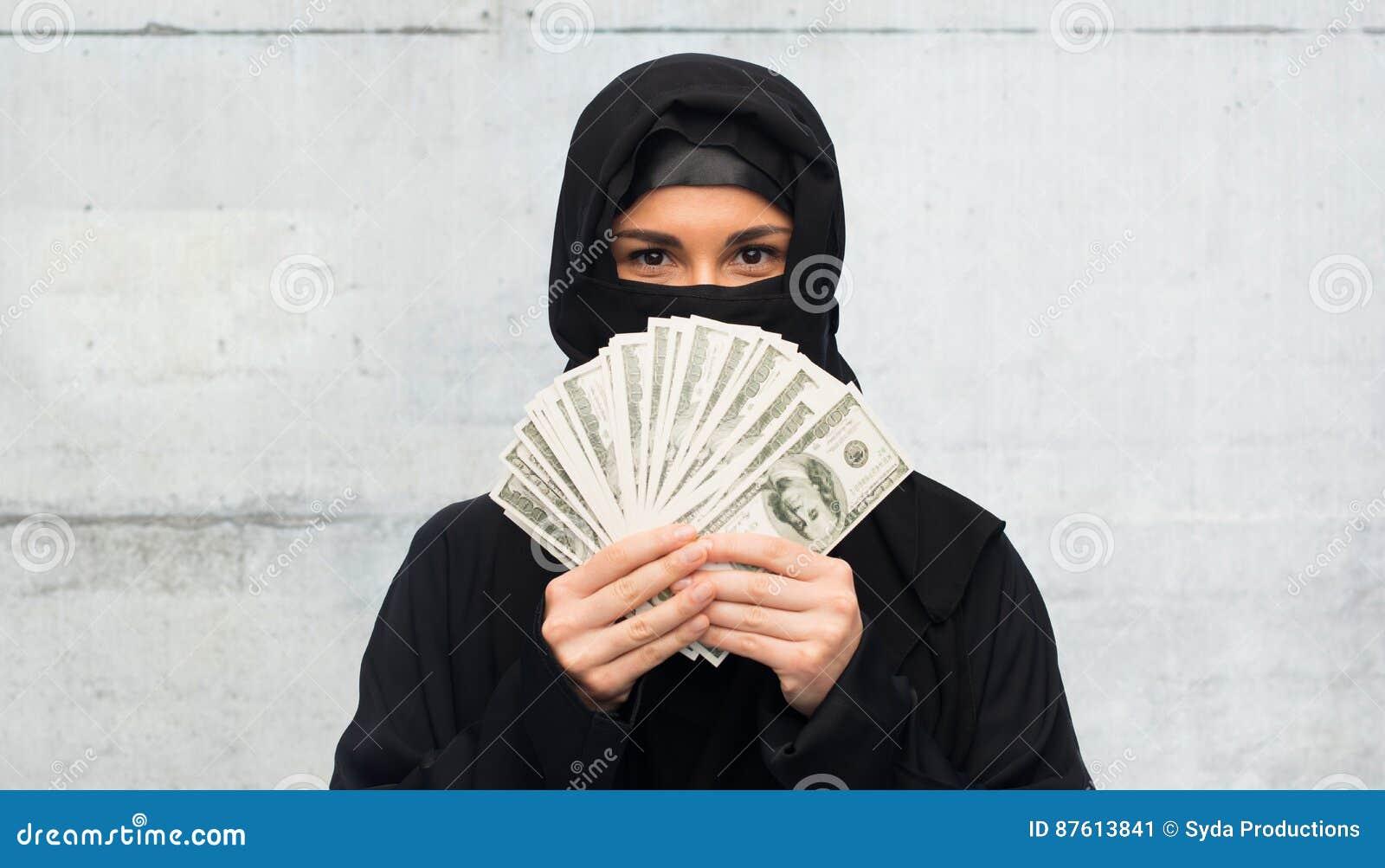 Mujer musulmán en hijab con el dinero sobre blanco