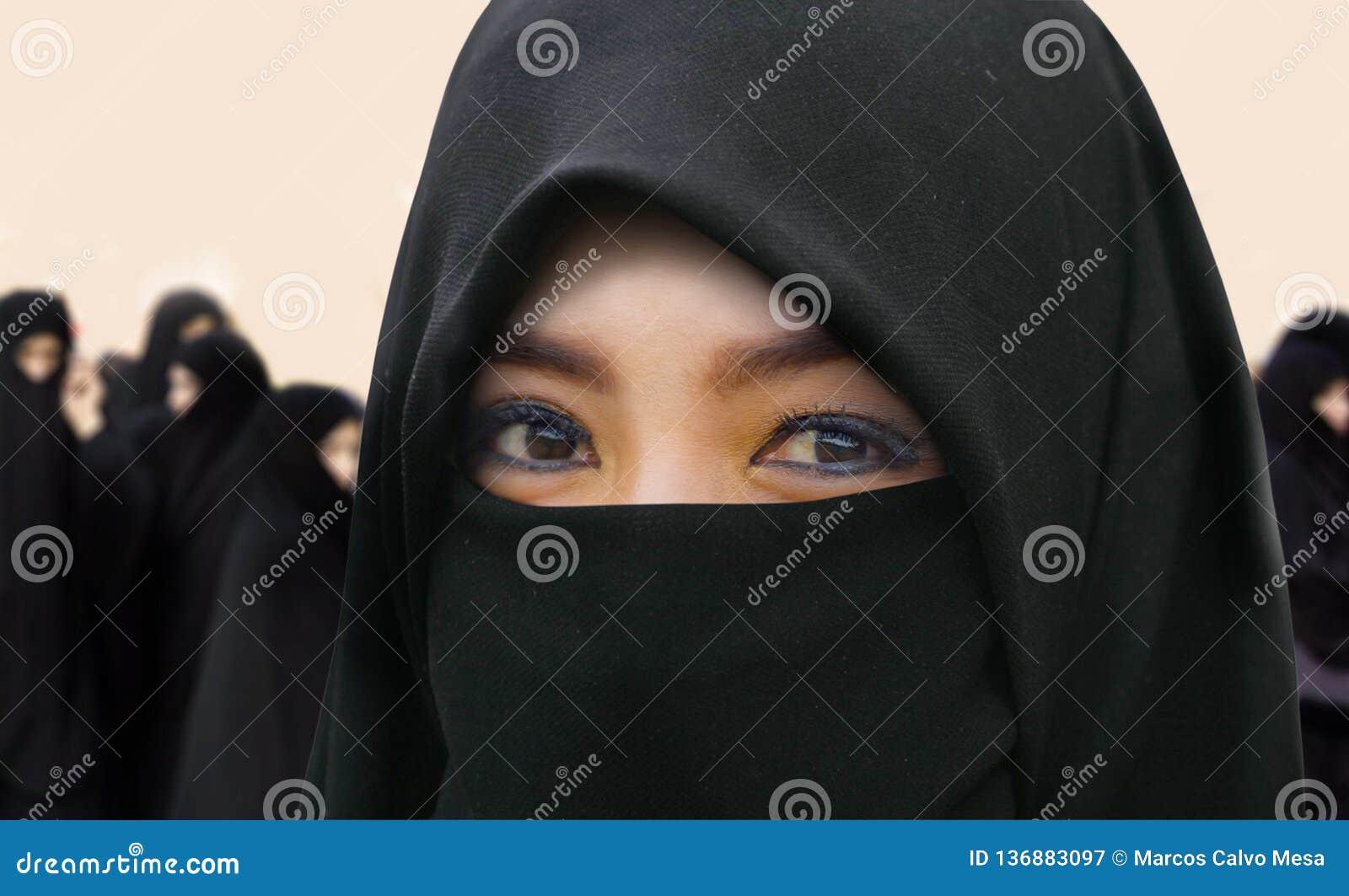 Mujer musulmán hermosa y feliz joven en vestido tradicional del burqa del Islam con sorprender los ojos expresivos que miran la c