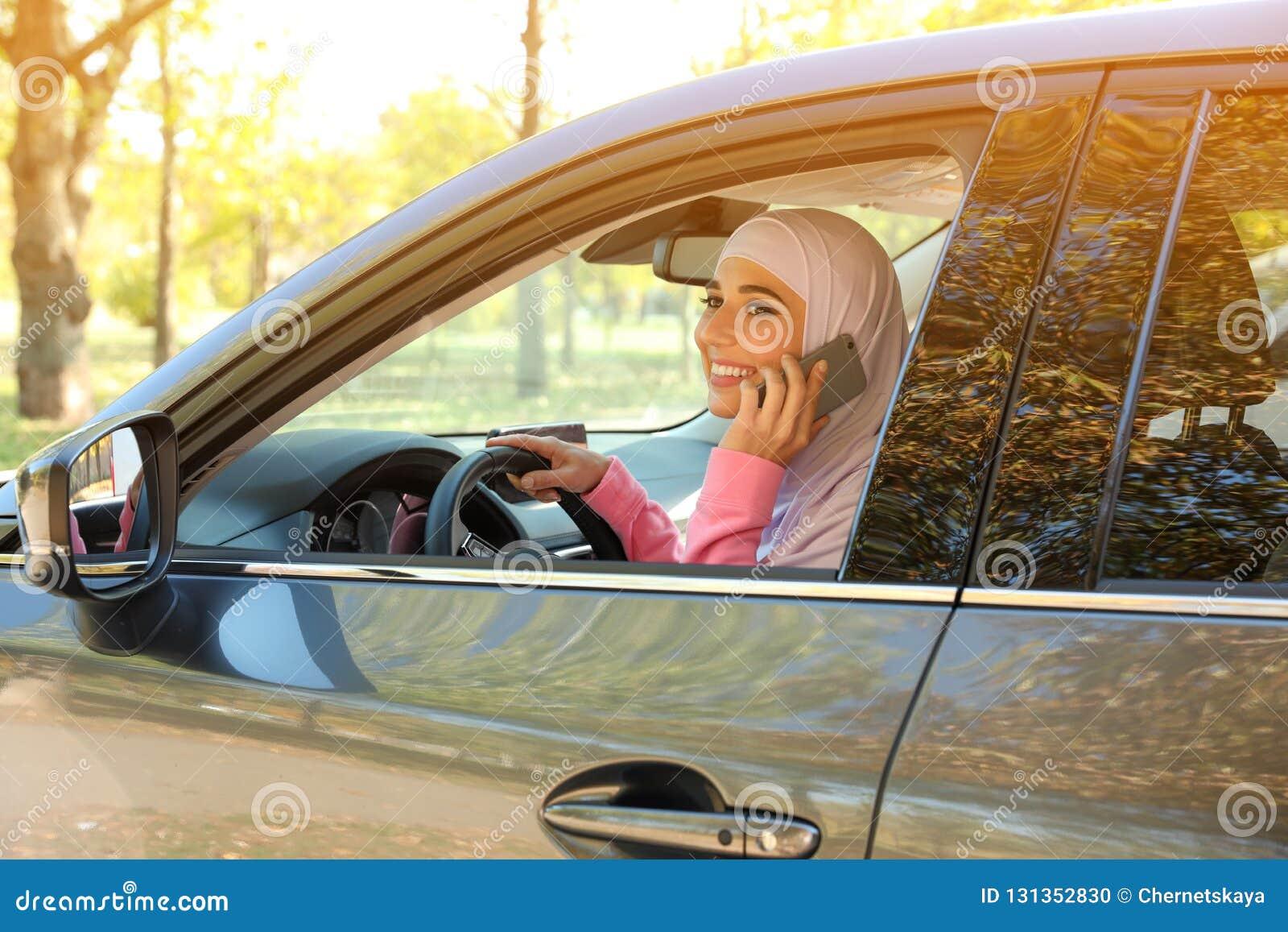 Mujer musulmán que habla en el teléfono en el asiento de conductor