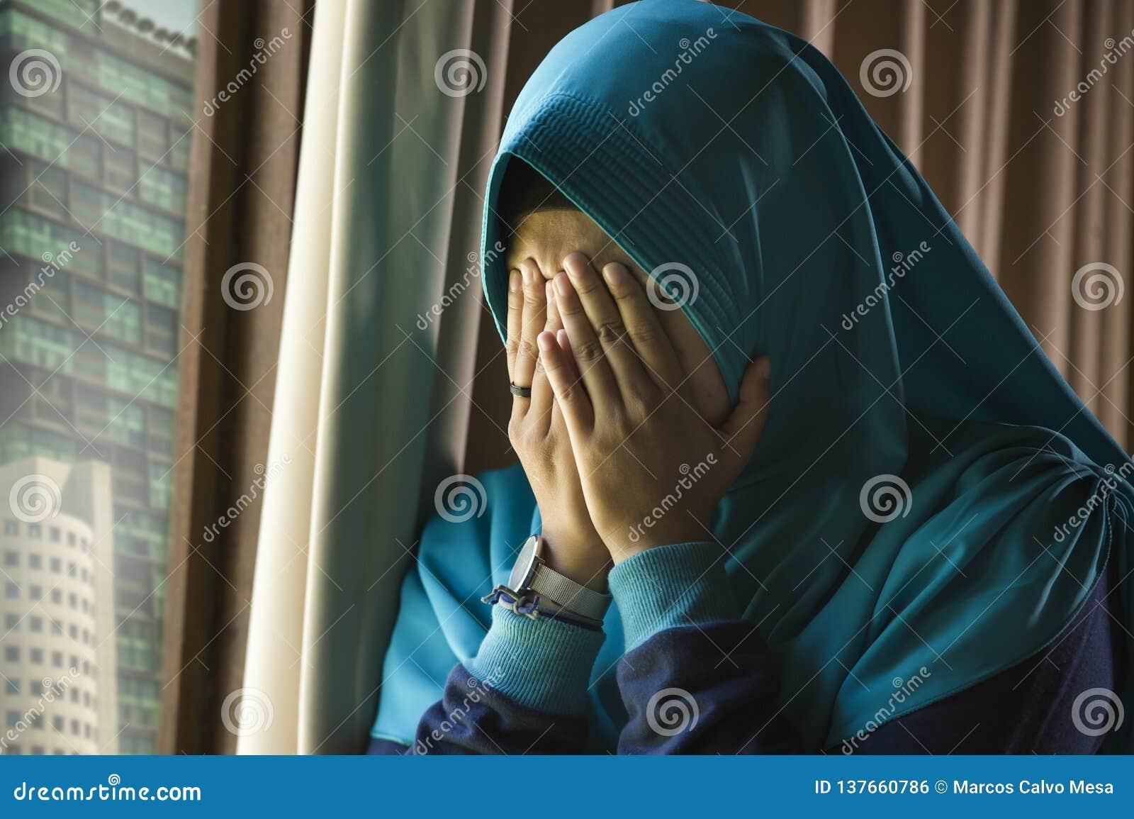 Mujer musulmán triste y deprimida joven en la ventana tradicional de la bufanda de la cabeza de Hijab del Islam en casa que sient