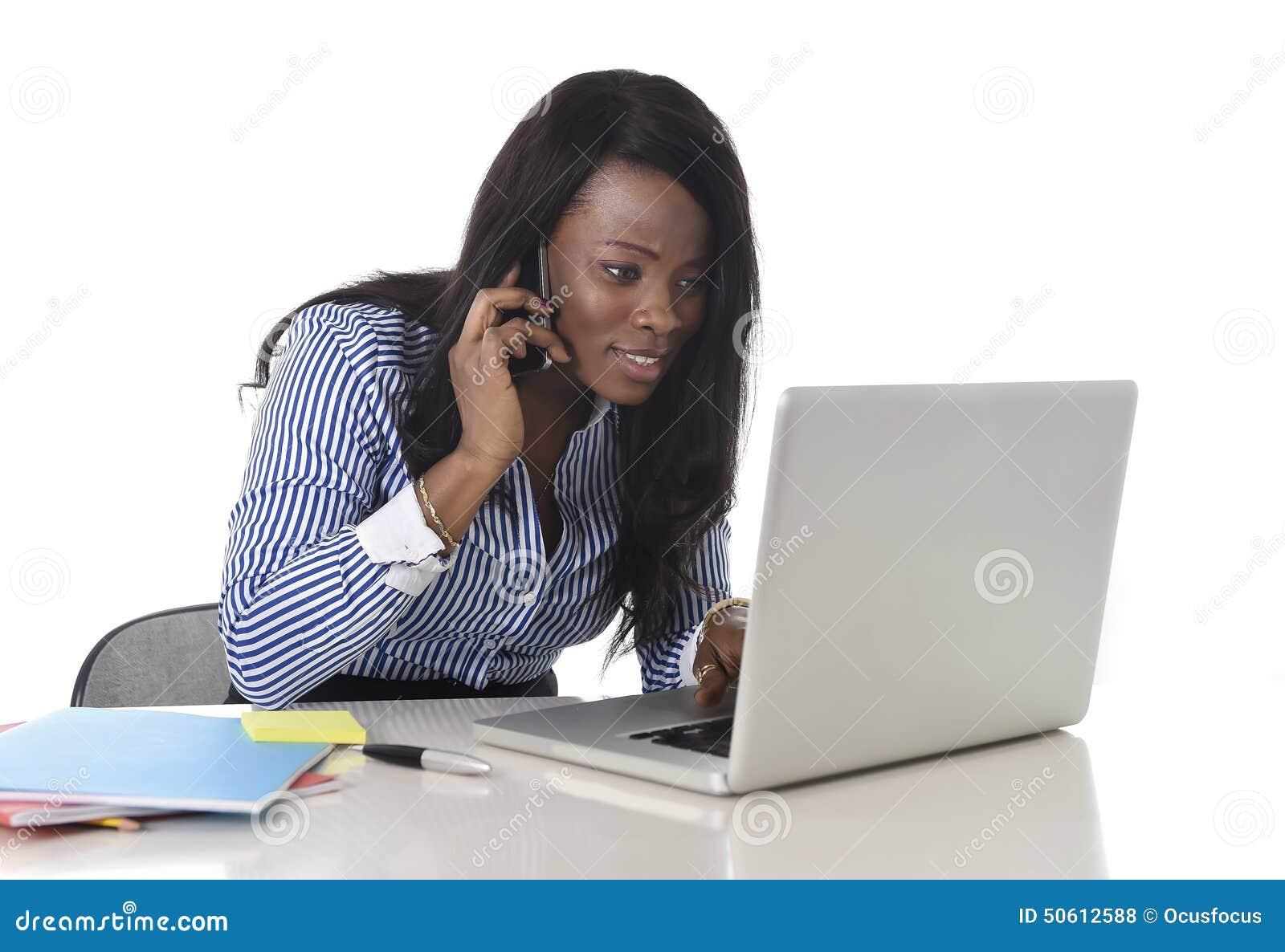Mujer negra feliz de la pertenencia étnica que trabaja en el ordenador portátil del ordenador y el teléfono móvil relajados