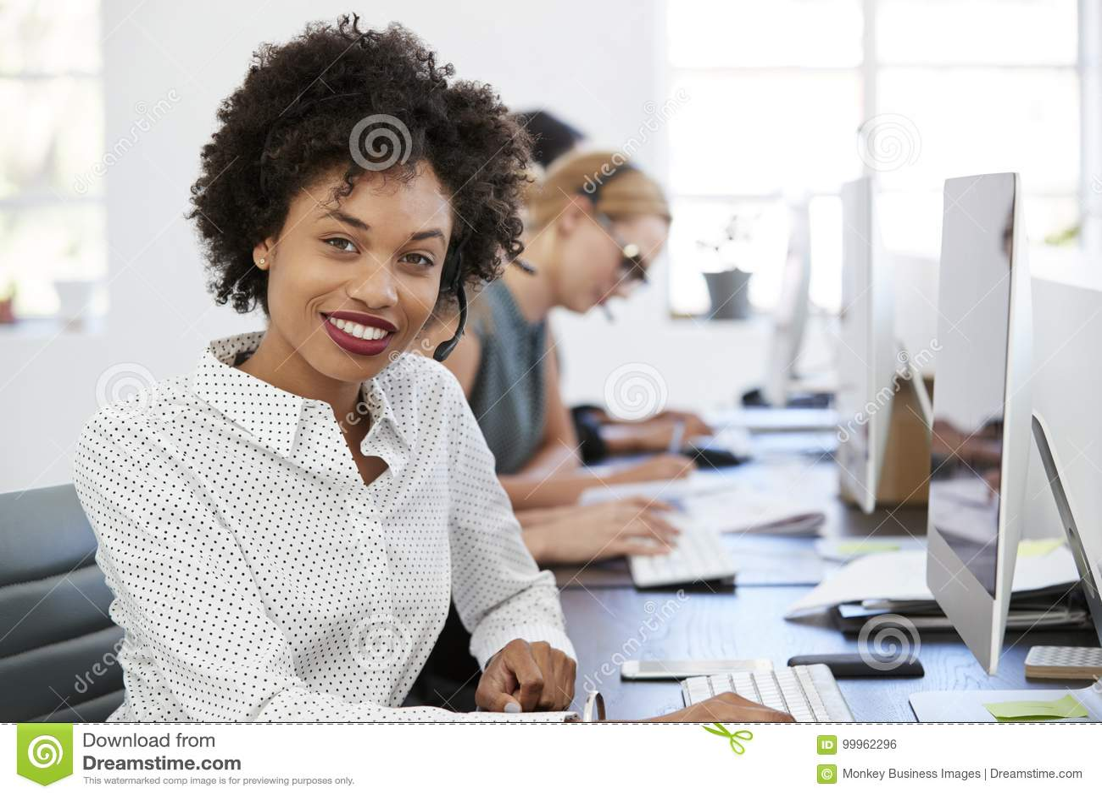 Mujer negra joven con las auriculares que sonríe a la cámara en oficina