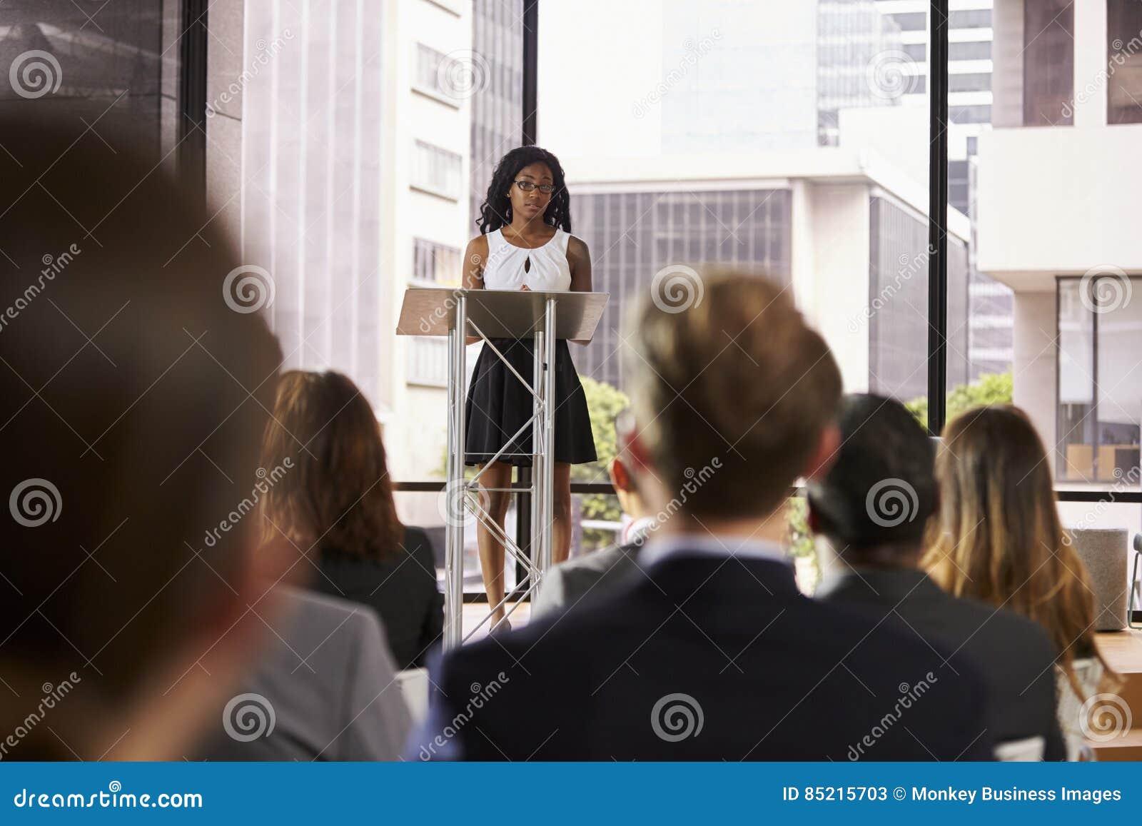 Mujer negra joven en el atril que presenta seminario a la audiencia