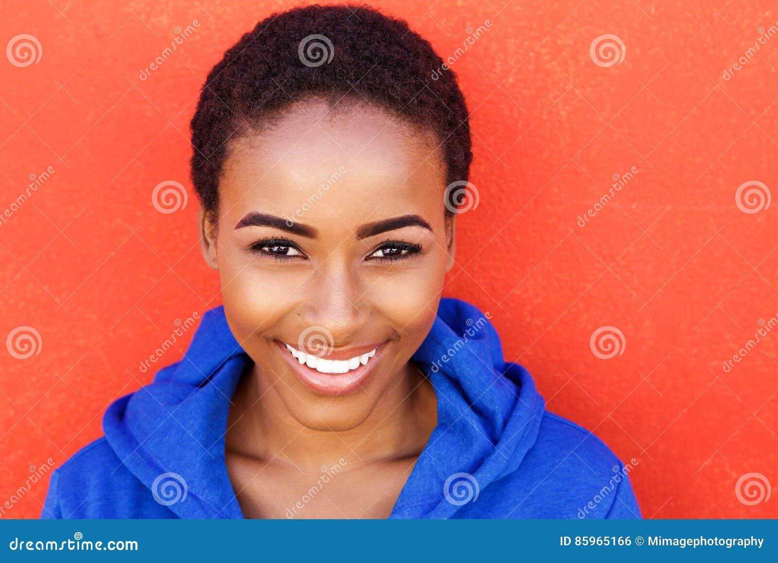Mujer negra joven hermosa de la moda que sonríe contra la pared roja
