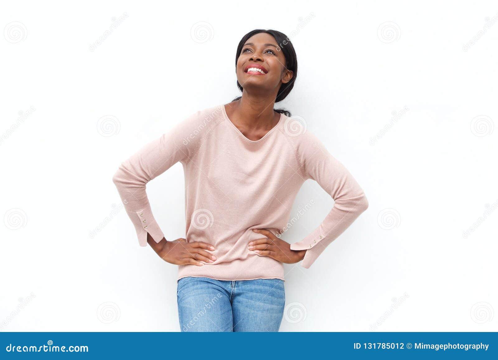 Mujer negra joven hermosa que sonríe con las manos en caderas y que mira para arriba