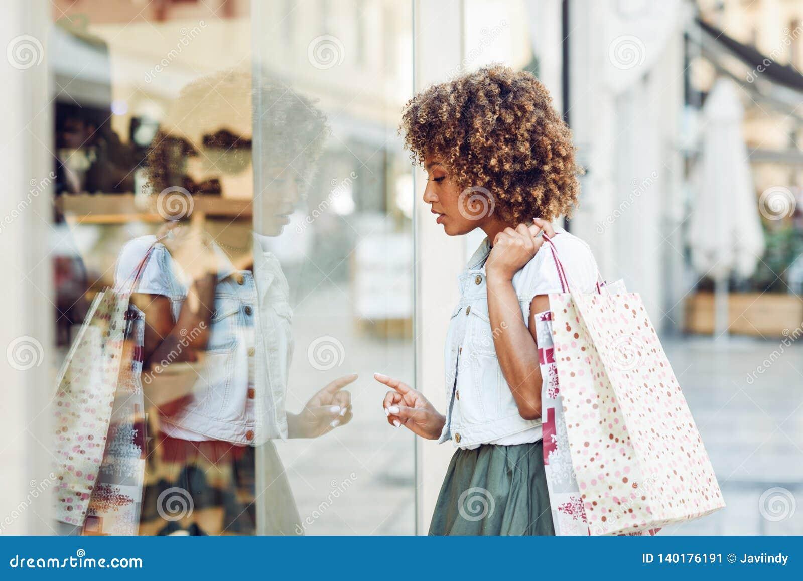 Mujer negra joven, peinado afro, mirando una ventana de la tienda
