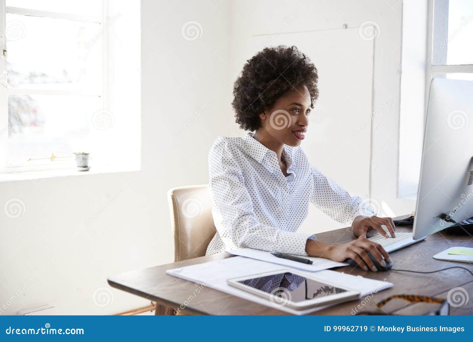 Mujer negra joven que elabora en el ordenador en una oficina, cierre