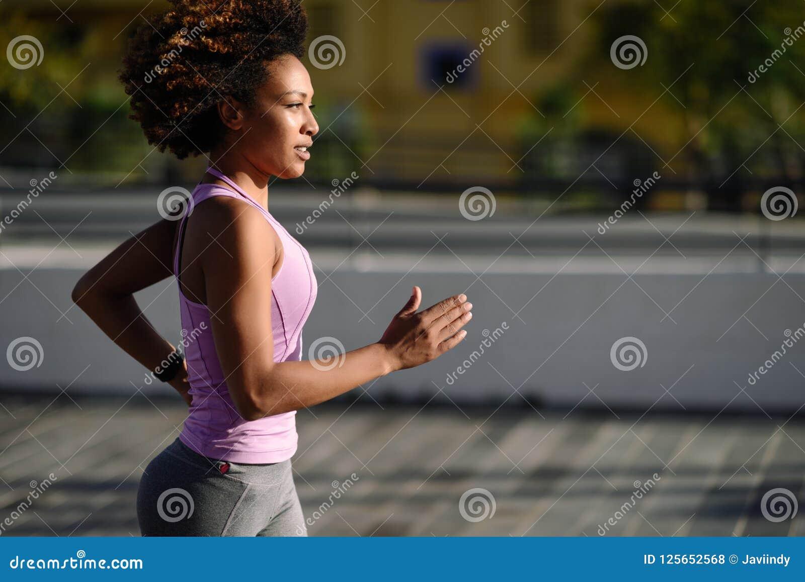 Mujer negra, peinado afro, corriendo al aire libre en camino urbano