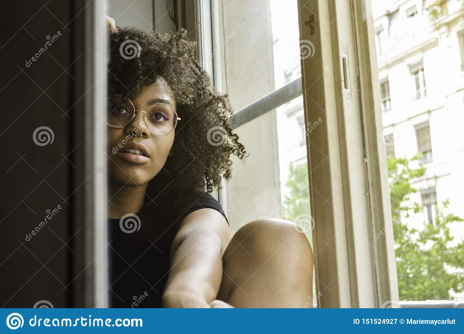 Mujer negra sensual atractiva joven que se sienta cerca de la ventana que mira la cámara
