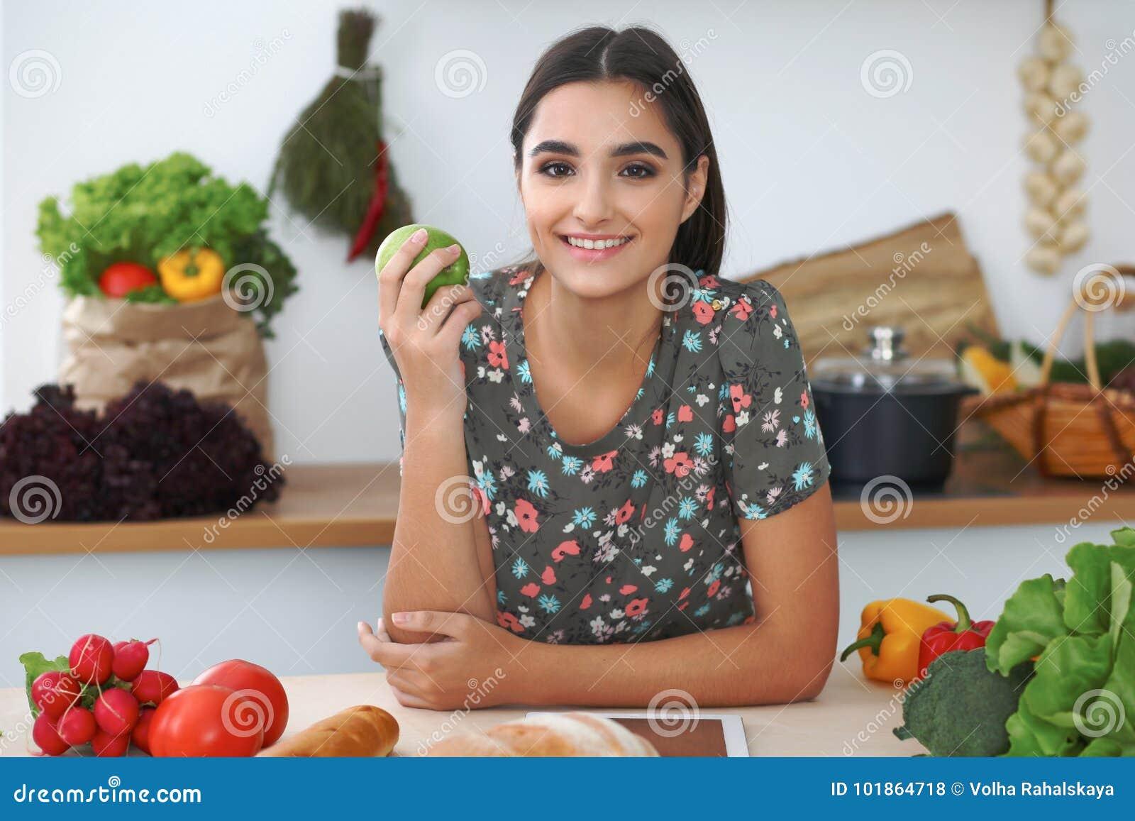 Mujer o estudiante hispánica joven que cocina en cocina Muchacha que usa la tableta para hacer compras en línea o para encontrar