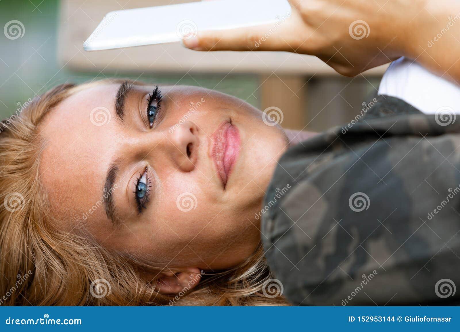 Mujer observada azul joven atractiva que miente en ella detrás