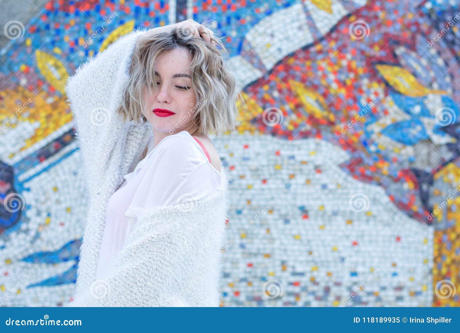 Mujer pecosa atractiva joven con los labios rojos en la presentación que camina blanca de la ropa casual en la calle
