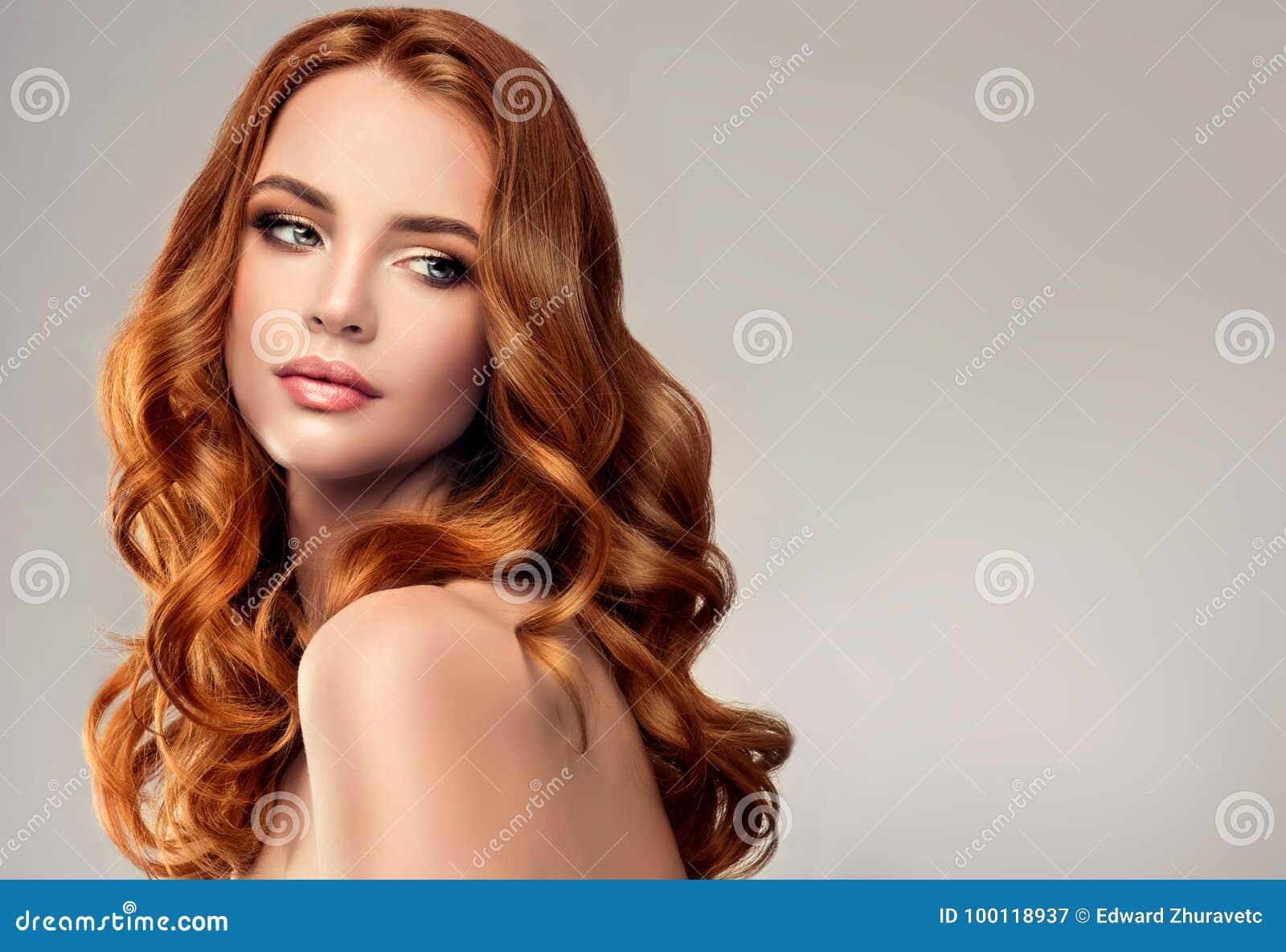 Mujer pelirroja con el peinado voluminoso, brillante y rizado Pelo del vuelo