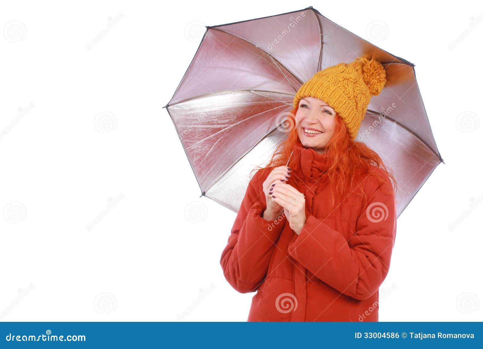 Mujer pelirroja joven en equipo casual con el paraguas