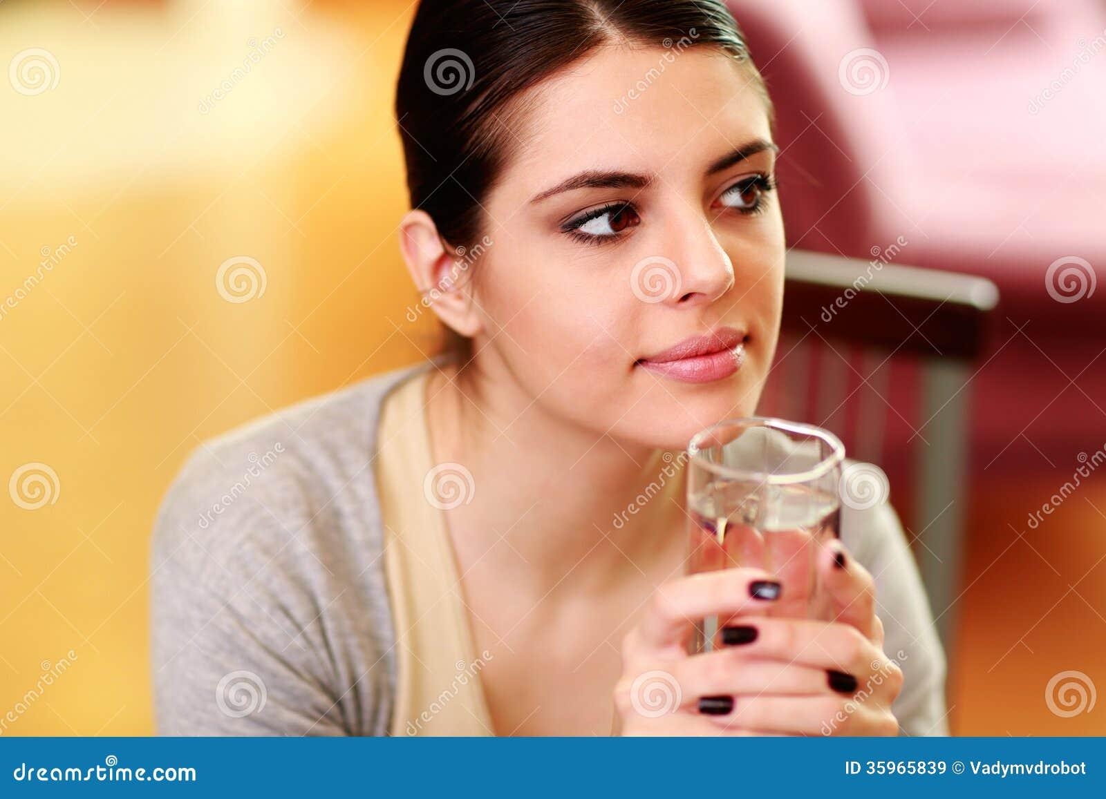 Mujer pensativa hermosa joven que se sostiene de cristal con agua