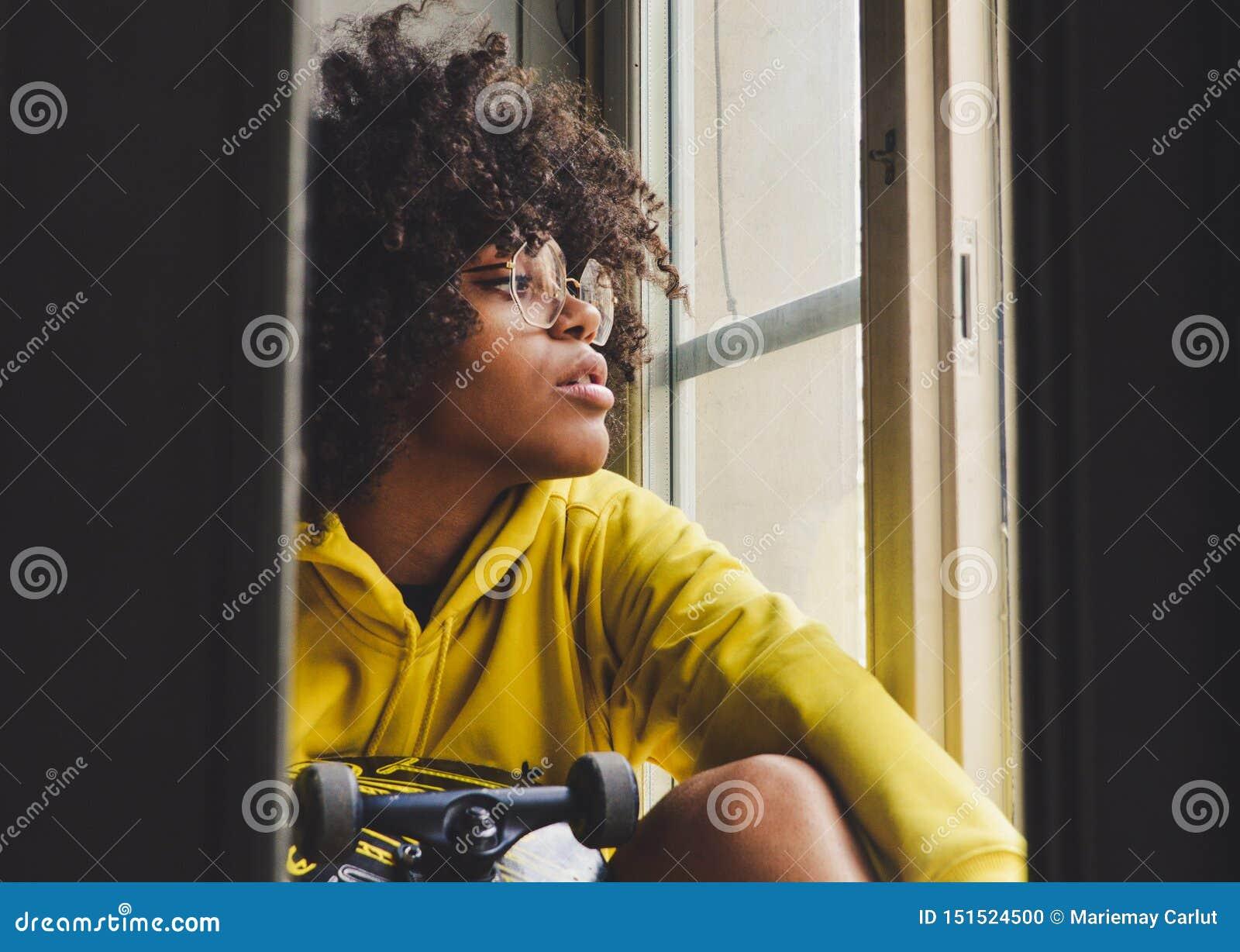 Mujer pensativa negra sensual joven elegante que se sienta cerca de la ventana con un monopatín