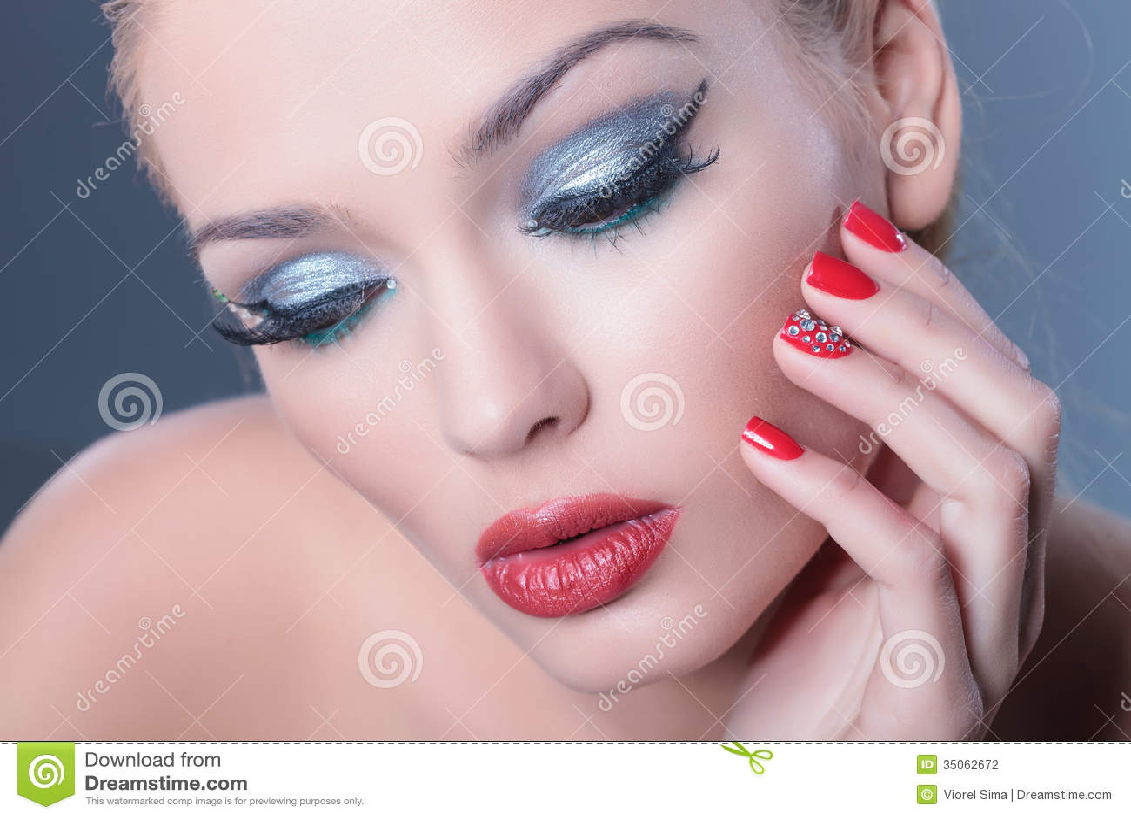 Mujer pensativa que lleva maquillaje agradable y los clavos rojos que miran abajo