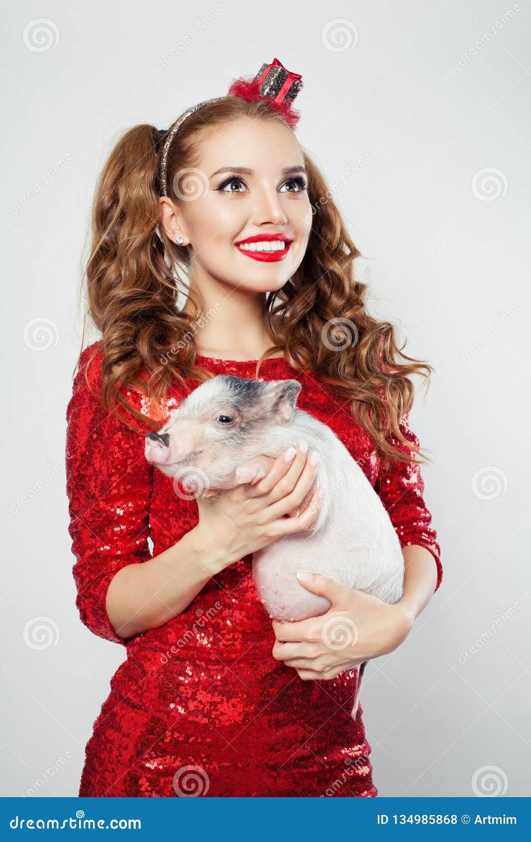 Mujer perfecta con el maquillaje que sostiene el mini cerdo, retrato de la moda